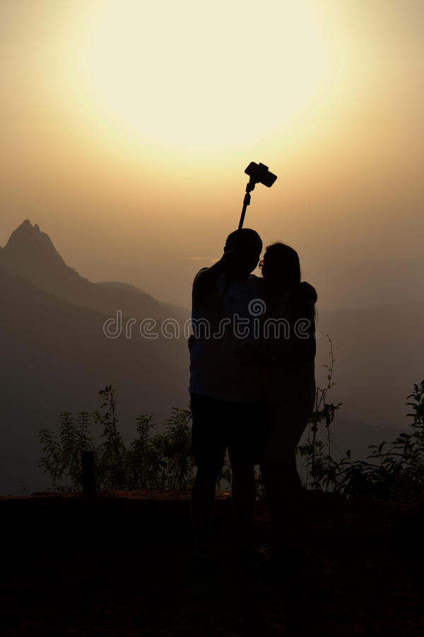 Tourist couple takes a selfie at sunset in the hills stock photos