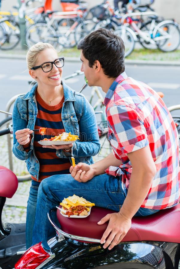Tourist couple taking rest during scooter tour eating currywurst royalty free stock images