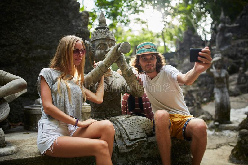 Tourist couple taking selfie with ancient buddhist statue in thailand royalty free stock photo