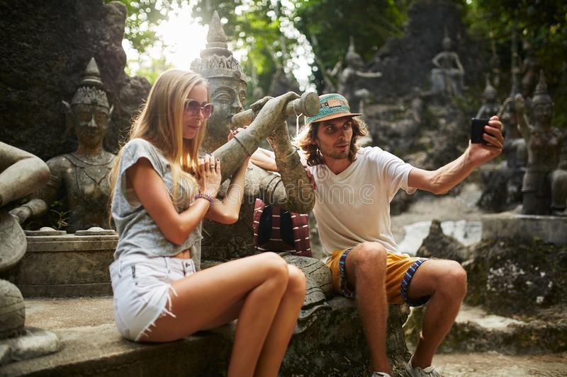 Tourist couple taking selfie with ancient buddhist statue in thailand royalty free stock images