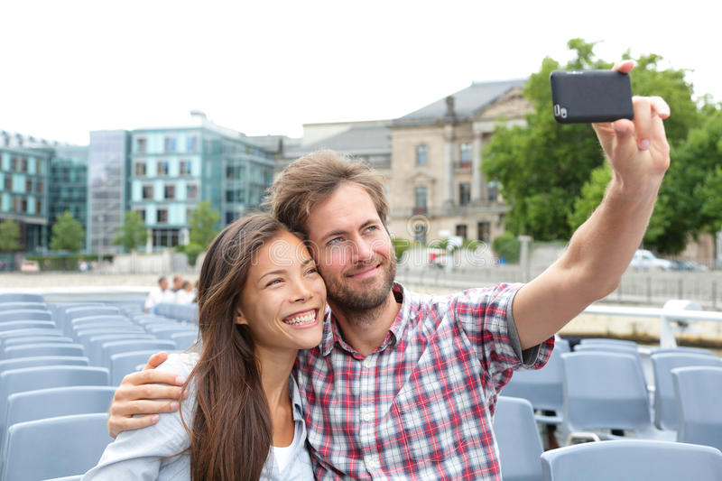 Tourist couple on travel in Berlin, Germany. On boat tour cruise smiling happy taking selfie self-portrait photo picture while enjoying their romantic Europe stock images