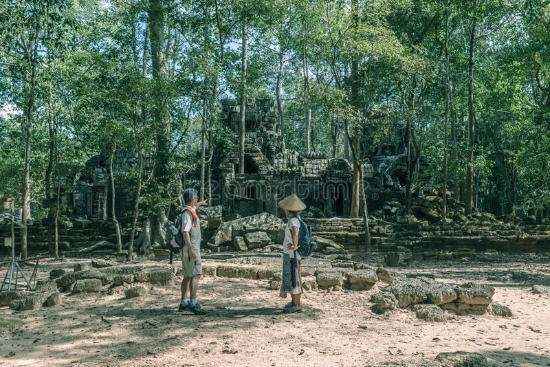 Tourist couple visiting Angkor temples, Cambodia. Ta Nei building ruins in the jungle. Eco friendly tourism traveling, toned image stock image