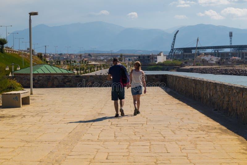 Tourist couple walking on the coastal road of heraklion crete royalty free stock photography