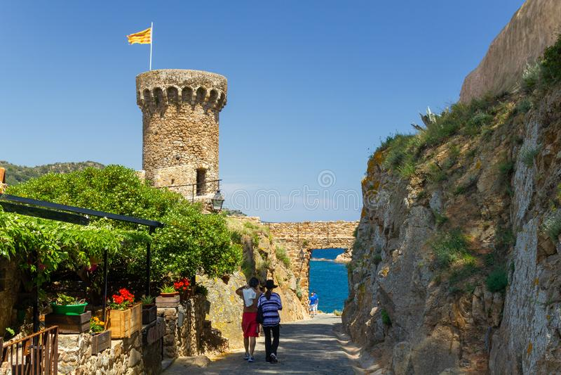 Tourist couple walking to sea at Tossa de Mar stock images