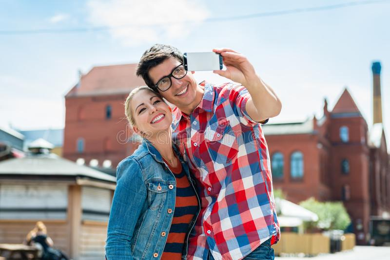 Tourist couple taking selfie on rooftop in Berlin. Tourist couple, women and man, taking holiday selfie on rooftop in Berlin stock images