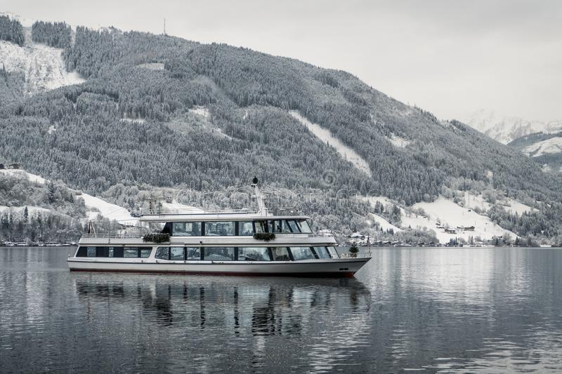 Tourist cruise in Austria Zell am See on frozen lake with snow and beautiful mountains on the background. Tourist ship boat s. Alling in winter time and royalty free stock photos