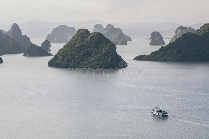 Tourist cruise ship sailing among limestone mountains in Halong Bay, Vietnam. Framing with tree leaves, boat, sea, vietnamese, ride, northern, beach, holiday royalty free stock image