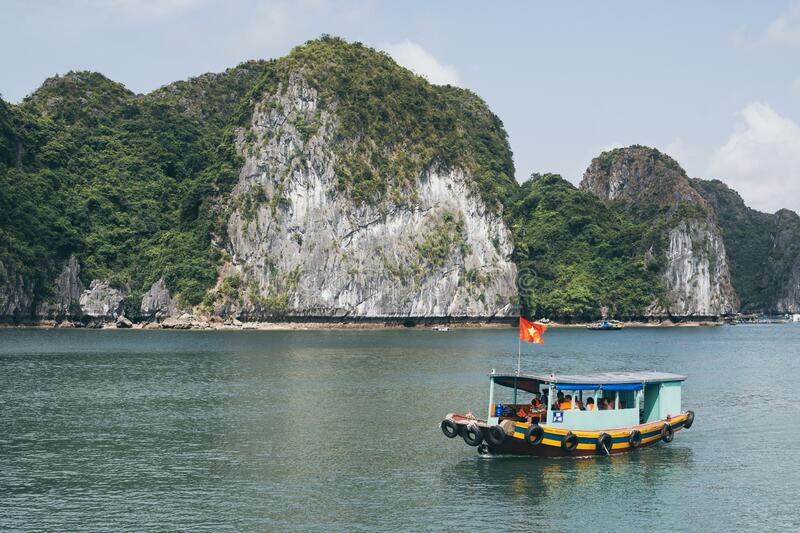Tourist cruise ship sailing among limestone mountains in Halong Bay, Vietnam. Framing with tree leaves, boat, sea, vietnamese, ride, northern, beach, holiday royalty free stock photos