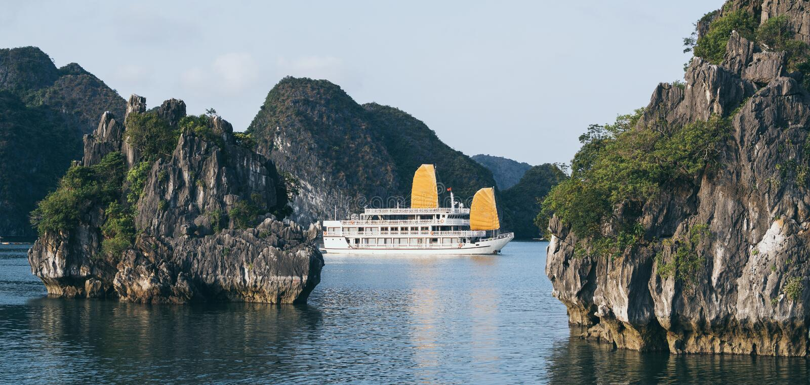 Tourist cruise ships sailing among limestone mountains in Halong Bay, Vietnam. Framing with tree leaves, boat, sea, vietnamese, ride, northern, beach, holiday royalty free stock image