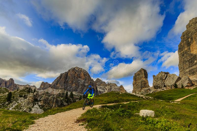 Tourist cycling in Cortina d`Ampezzo, stunning Cinque Torri and stock photography