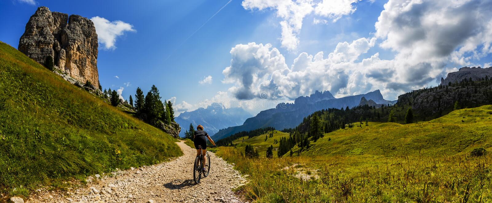 Tourist cycling in Cortina d `Ampezzo, stunning rocky mountains on the background. Woman riding MTB enduro flow trail. South Tyrol royalty free stock images