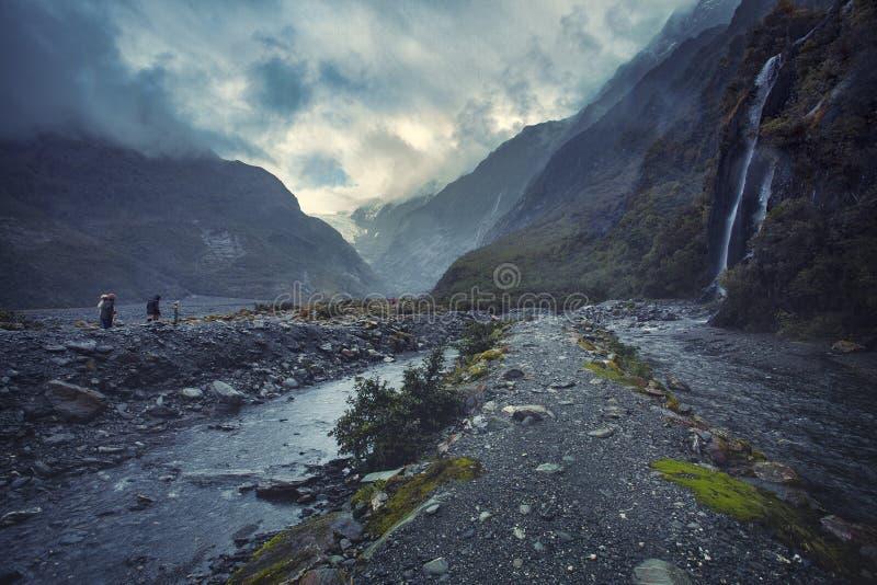 Tourist, der auf Spur zu Gletscher Franz Josef im nebeligen Wetter geht stockbild