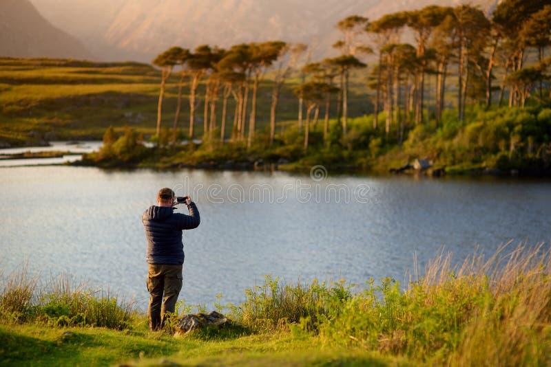 Tourist, der die Ansicht von zwölf Kiefern Insel, Connemara, Grafschaft Galway, Irland bewundert stockfoto