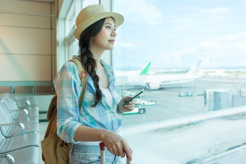Tourist, der am Flughafenfenster aufpasst stockfoto