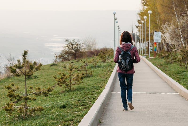 Tourist der jungen Frau, der auf Straße im Park geht Hintere Ansicht lizenzfreie stockfotografie