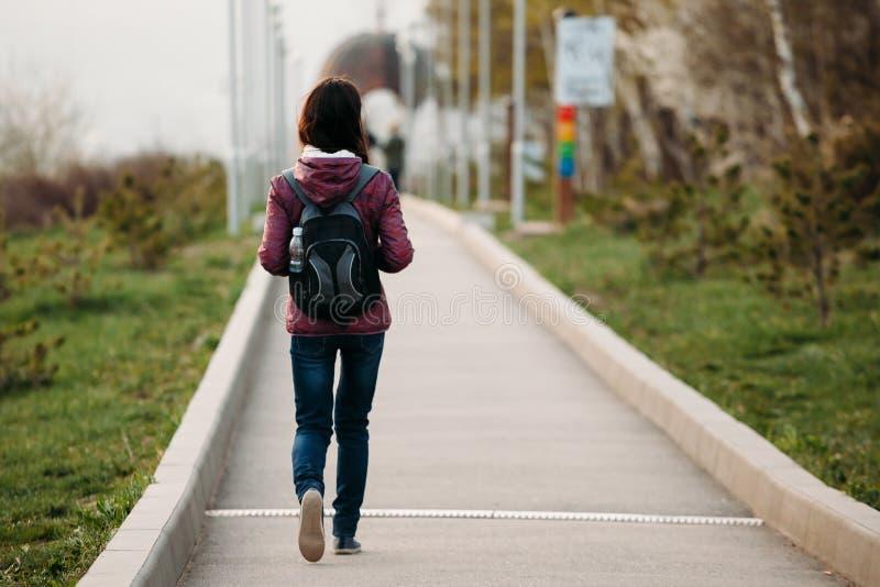 Tourist der jungen Frau, der auf Straße im Park geht Hintere Ansicht lizenzfreie stockbilder
