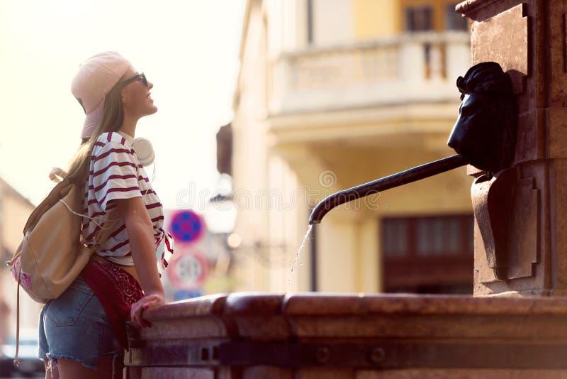 Tourist der jungen Frau, der durch den allgemeinen Brunnen an einem heißen Sommertag erneuert stockbild