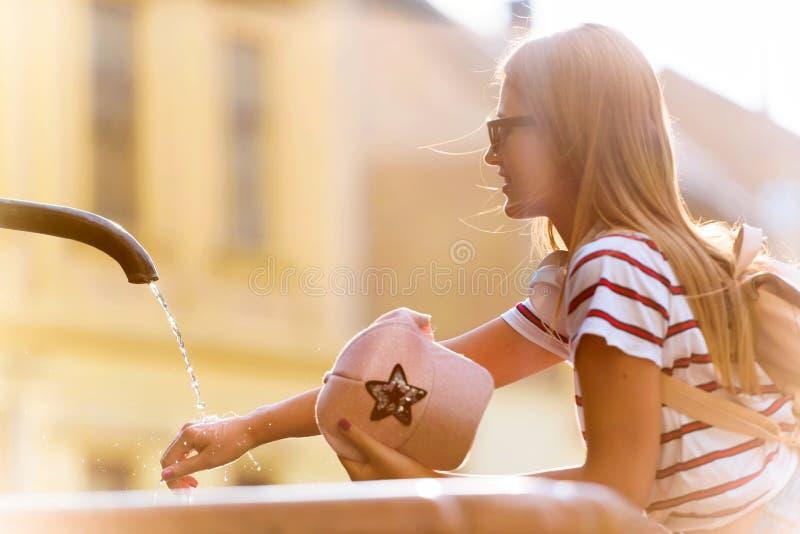 Tourist der jungen Frau, der durch den allgemeinen Brunnen an einem heißen Sommertag erneuert lizenzfreies stockbild