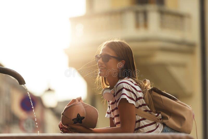 Tourist der jungen Frau, der durch den allgemeinen Brunnen an einem heißen Sommertag erneuert stockbilder