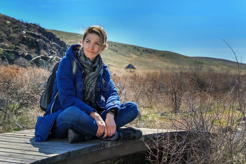 Tourist der jungen Frau sitzt und steht auf einer alten Holzbrücke auf einem Hintergrund von Bergen still lizenzfreies stockfoto