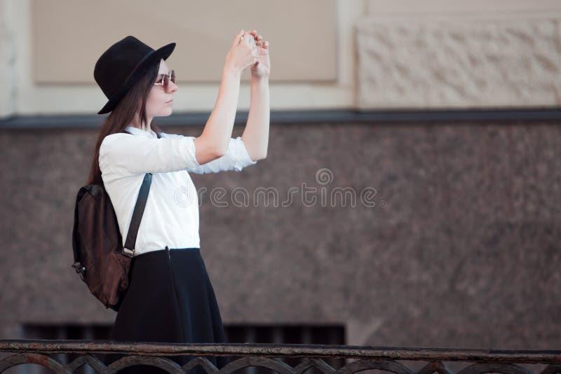 Tourist in der Stadt macht ein Foto auf Smartphone Eine junge Frau in einem schwarzen Hut und in einem weißen Hemd, stockfotografie