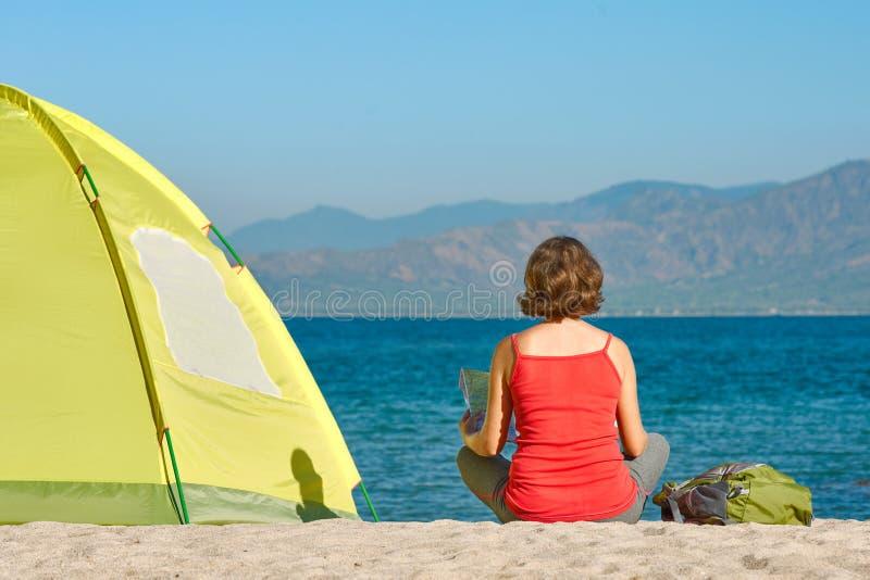 Tourist des jungen Mädchens sitzen nahe dem Zelt, welches die Karte schaut stockfotos