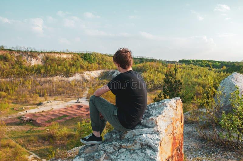 Tourist des jungen Mannes, der auf dem riesigen Felsen, auf die Oberseite des Berges sitzt stockfotografie