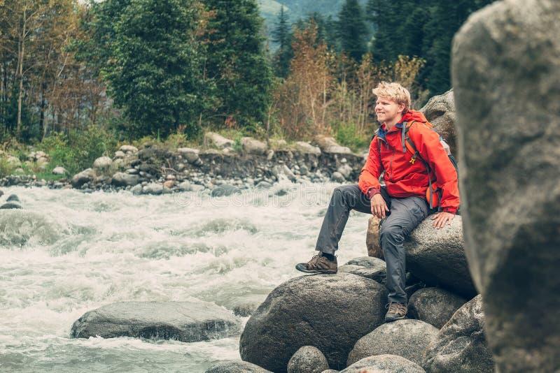 Tourist des jungen Mannes sitzt felsige Gebirgsflussbank stockbild