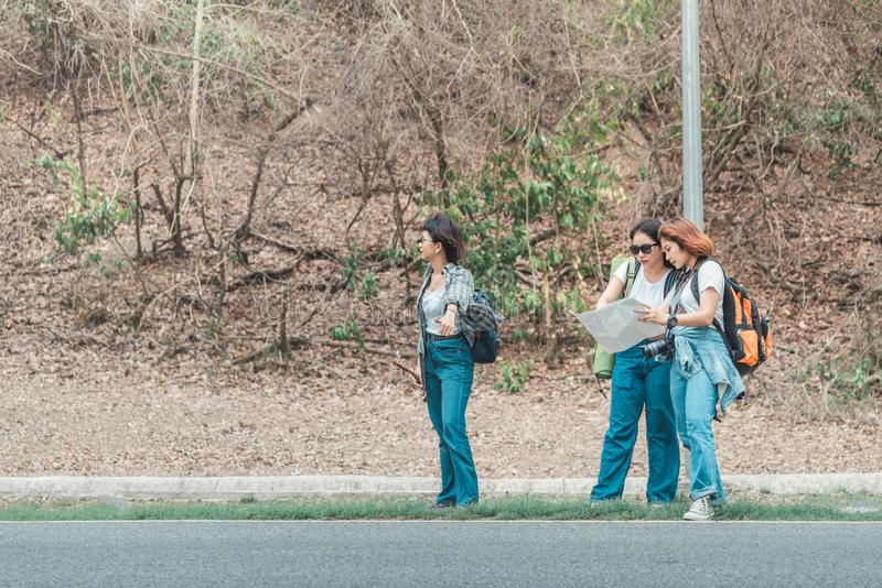 Tourist drei, welche einer Straße mit Karte und nach Uhr im Wald mit Rucksack sucht stockfoto