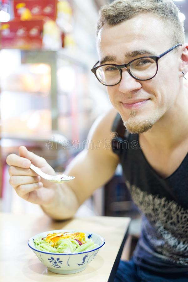 Tourist eating cendol dessert. Young tourist eating cendol ais Kachang dessert in Mallaca city. Traditional shaved ice snack of Malaysia stock photo