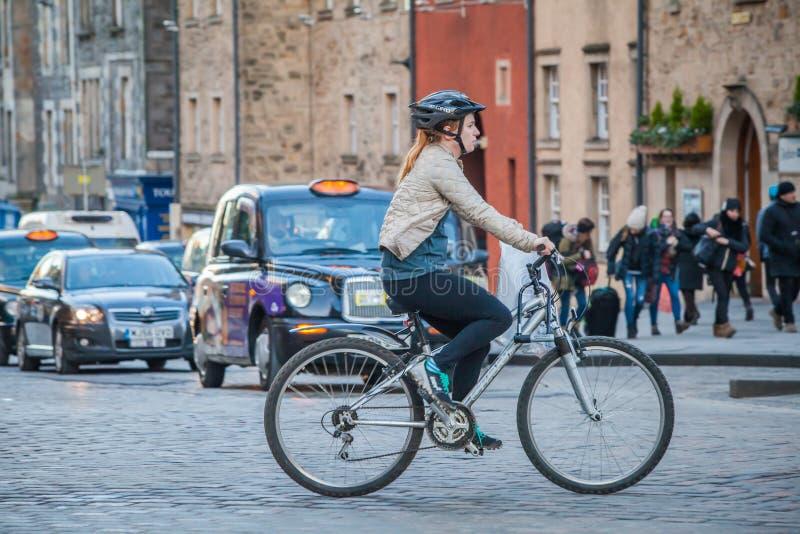 Tourist in Edinburgh riding bike royalty free stock photo