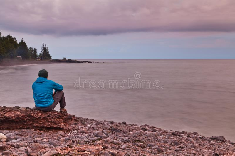 Tourist sitting on rocky shore of Lake Superior and enjoy scenic view. Tourist enjoy his solitude on the rocky shore of Lake Superior in Michigan`s Upper stock image