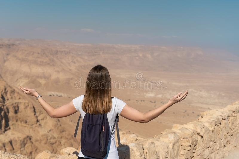 Young woman with arms raised looking the panorama over the desert in israel. Tourist enjoying freedom in the desert of israel. panoramic view royalty free stock images