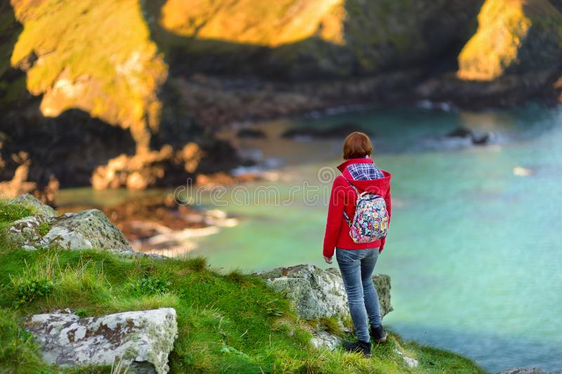 Tourist enjoying view of rugged Cornish coastline near Port Isaac historic fishing village on sunny morning, Cornwall, England. Tourist enjoying view of scenic royalty free stock images
