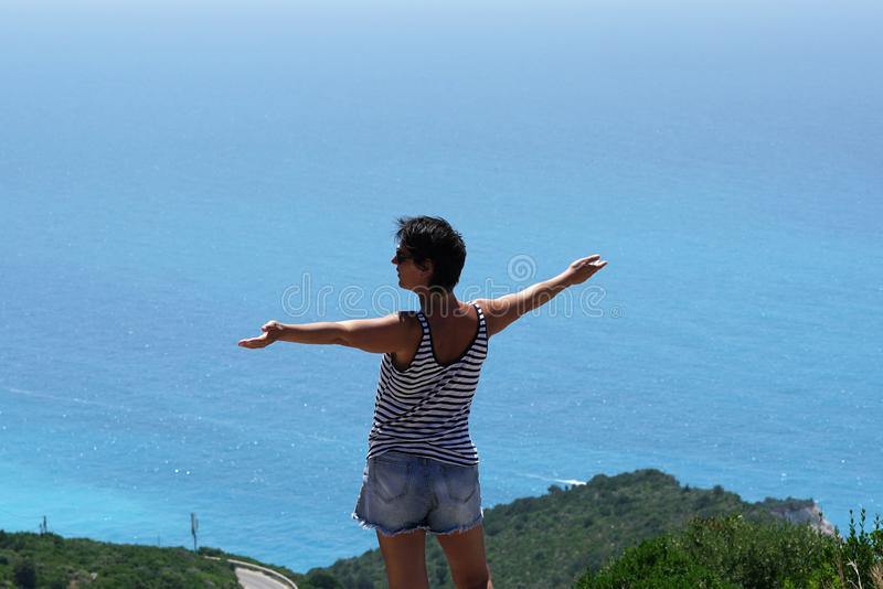A tourist enjoys the splendid view of the panorama of Porto Katsiki in Lefkada royalty free stock photos