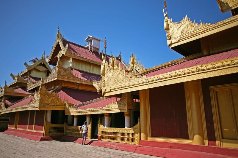 A tourist explores the golden spires and roof of the historical wooden buildings within the central palace complex of the Mandalay royalty free stock photo