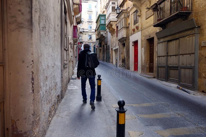 Tourist Exploring Streets of Valletta Malta. A man with a backpack, walks the narrow ancient streets of Valletta, the capital city of Malta. Typical Maltese royalty free stock photos