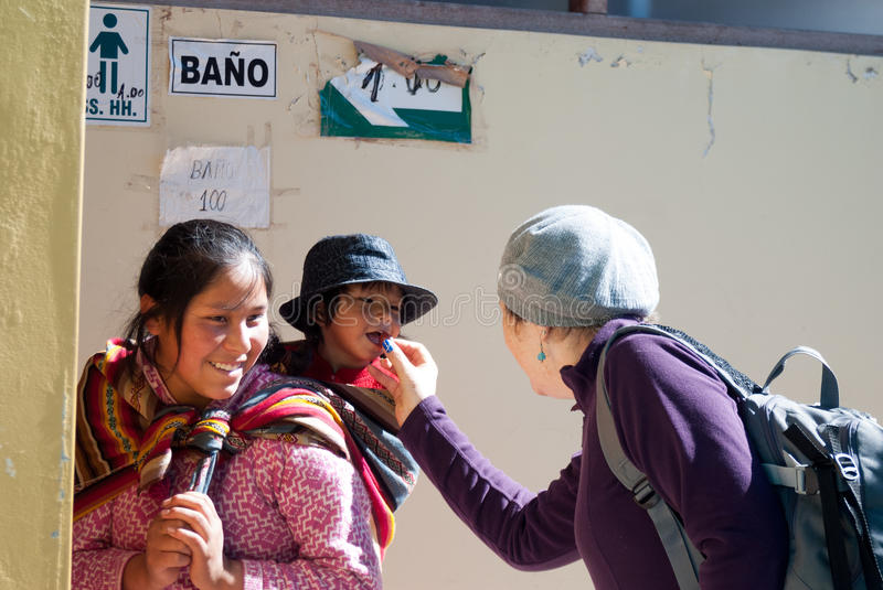 Tourist feeding a cute girl in a small village of Cusco, Peru royalty free stock image