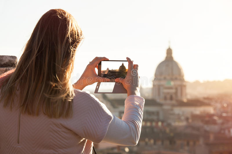 Tourist female taking picture smartphone. Travel to Rome, italy stock photography