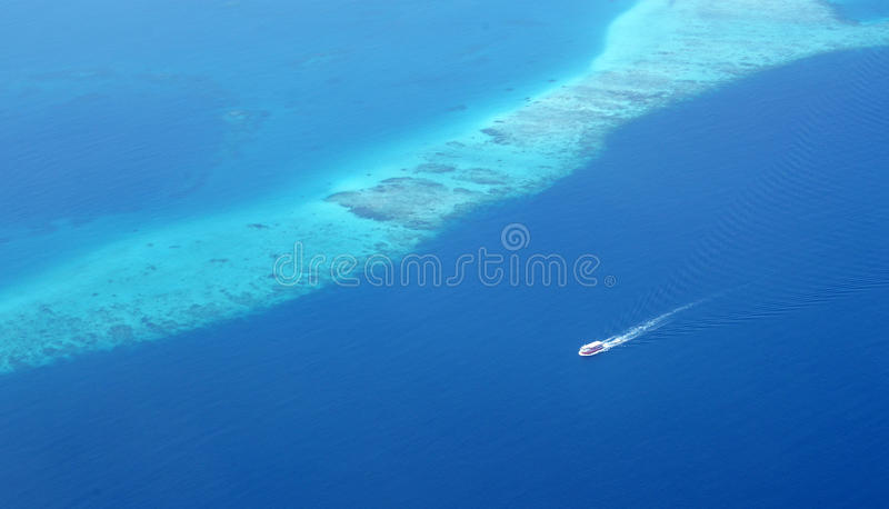 Tourist ferry boat running along a coral reef barrier. In one of Maldives` atoll. The water is beautifully in deep blue color and so crystal clear that we can royalty free stock image
