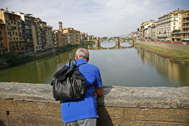 Tourist Florence. Retired man standig at Ponte Vecchio - Florence - Italy enjoying what he see while he feels the wings of history royalty free stock photo