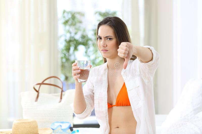 Tourist forbiding non-potable tap water in an hotel. Angry tourist forbiding non-potable tap water in an hotel room during a travel on summer vacations royalty free stock photos