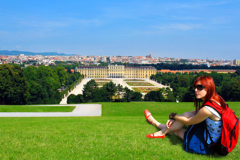 Young woman tourist with backpack, sitting on a lawn on a hill overlooking the beautiful Shoenbrunn castle in Vienna, Austria stock image