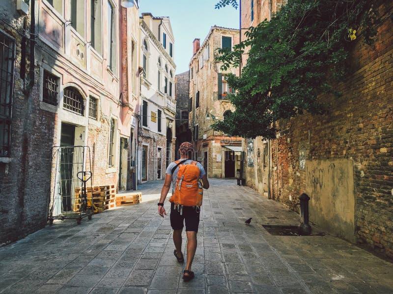 Tourist geht eine Ansicht mit seinem zurück zu Venedig, Italien mit einem orange Rucksack und einer Kamera auf seinem Hals entlan stockfotos