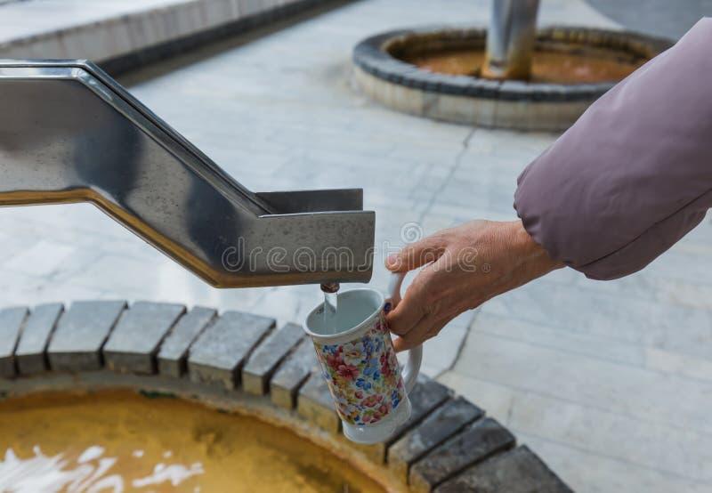 Tourist gießt Mineralwasser von der Quelle in Karlovy Vary - CZ stockfotografie