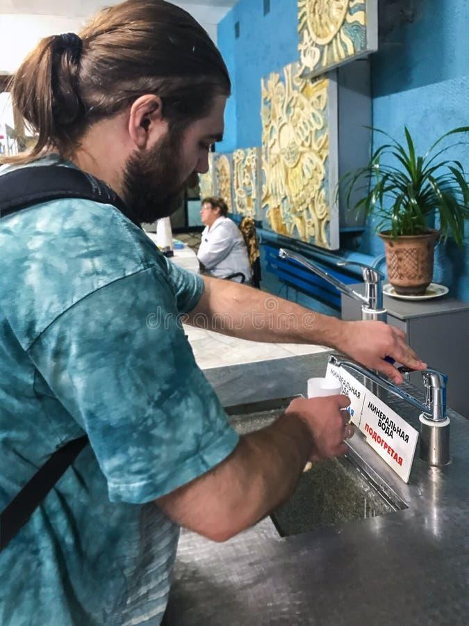 Tourist gießt Wasser in ein Glas in Pyatigorsk stockfotografie