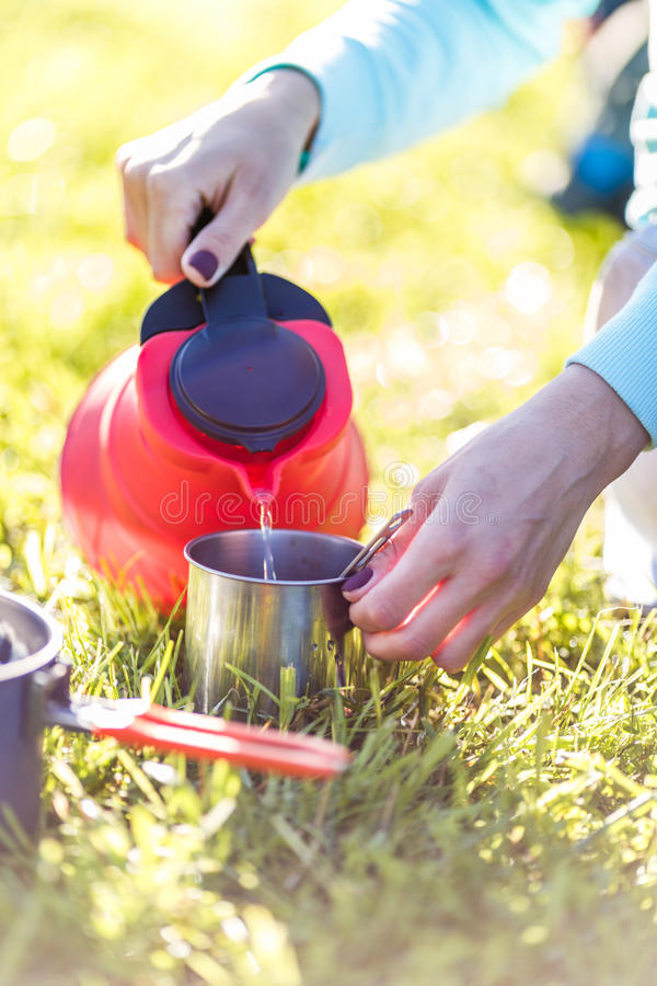 Tourist gießt Wasser vom Kessel lizenzfreie stockbilder