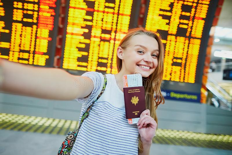 Tourist girl in airport, taking funny selfie with passport. Beautiful young tourist girl in international airport, taking funny selfie with passport and boarding stock photo