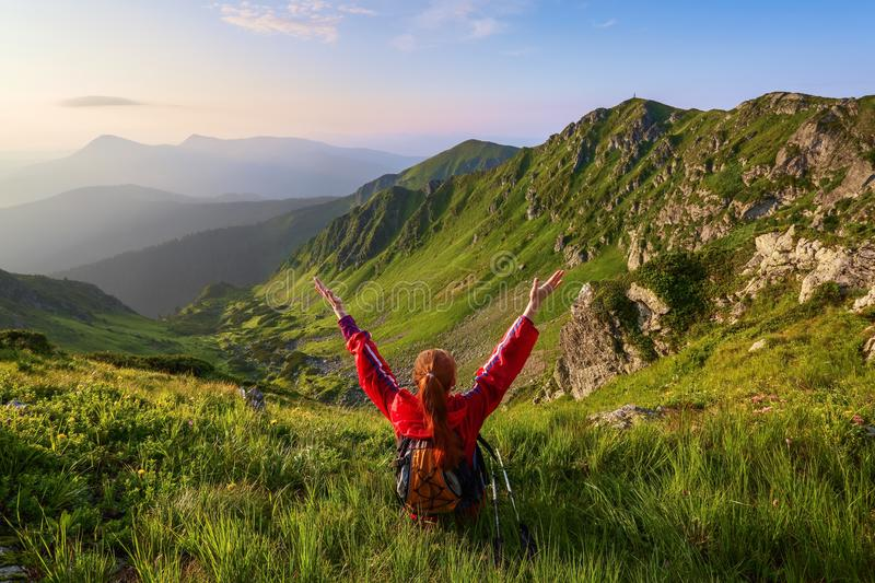 The tourist girl with back sack and tracking sticks sits on the lawn. Relaxation. Mountain landscapes. Wonderful summer day. royalty free stock photos