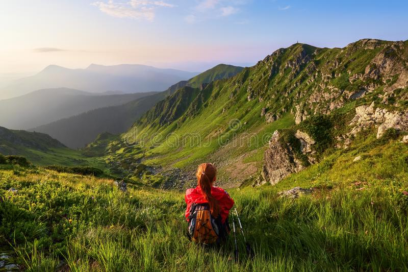 The tourist girl with back sack and tracking sticks sits on the lawn. Relaxation. Mountain landscapes. Wonderful summer day. royalty free stock image
